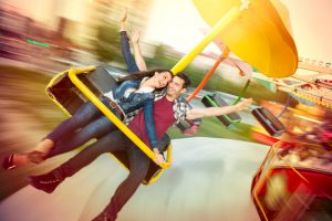 Young happy couple having fun at amusement park, riding on carousel