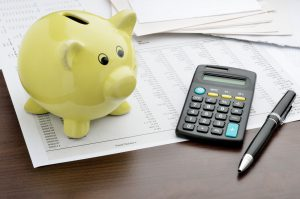 Piggy bank with calculator and business reports