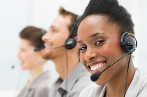 Closeup Of Happy Telephone Operator with Her Colleagues